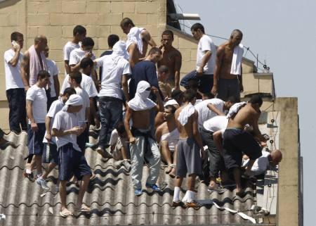 06-10-15 - REBELIÃO LONDRINA, Vários deles ocupam o telhado do presídio, encapuzados e armados.