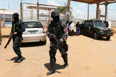 Riot police officers patrol outside a prison after clashes between rival criminal factions in Boa Vista