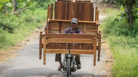 A furniture maker delivers beds and tables on a motorbike near Sragen, Central Java